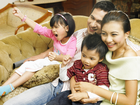 Husband and wife sitting, laughing together with children