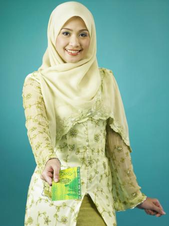 Single malay woman handing out envelop