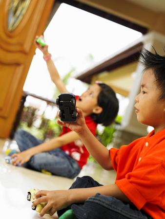 Siblings playing toy cars Stock fotó