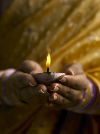 close up of hands holding oil lamp