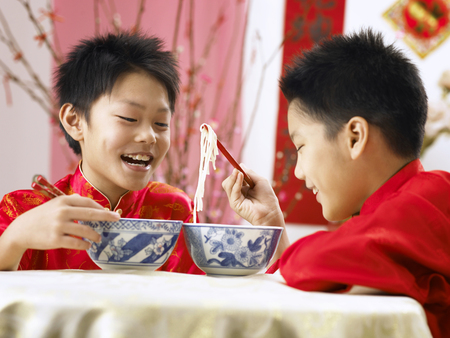 two boys eating longevity noodle Stock Photo