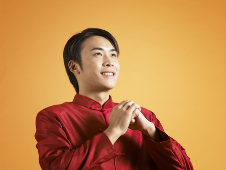 man in traditional costume greeting for chinese new year 版權商用圖片