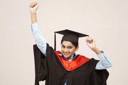 young graduate with arms raised