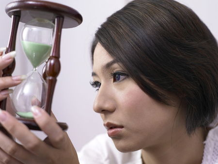 close up of woman holding a hourglass