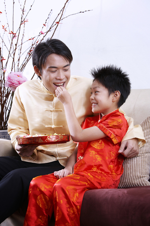 boy feeding candy to his father Stock Photo