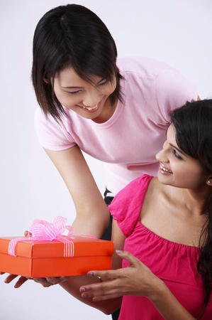 woman giving away a present to her friend