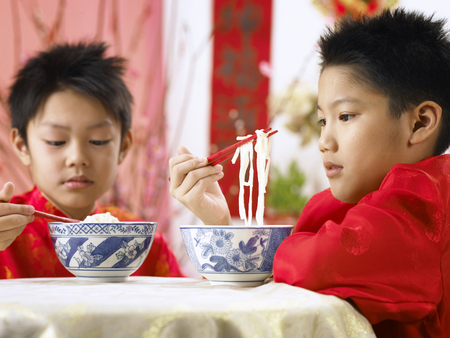 boys holding noodle with chopsticks
