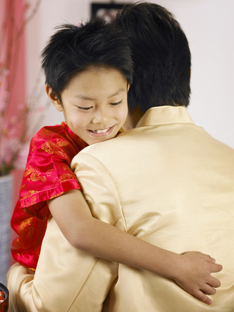 father embraces his son during chinese new year 版權商用圖片