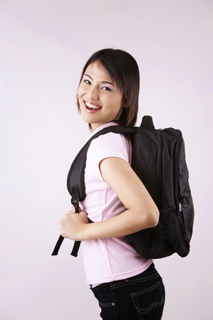 girl with backpack on the plain background 版權商用圖片