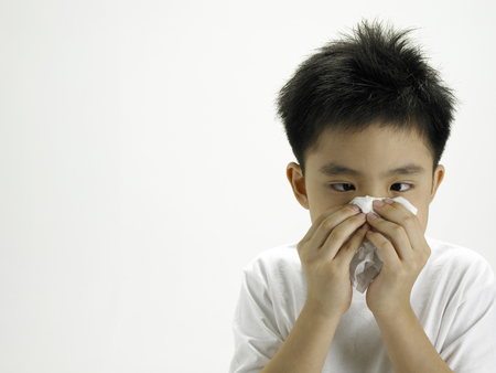 boy having cold he is wiping his nose
