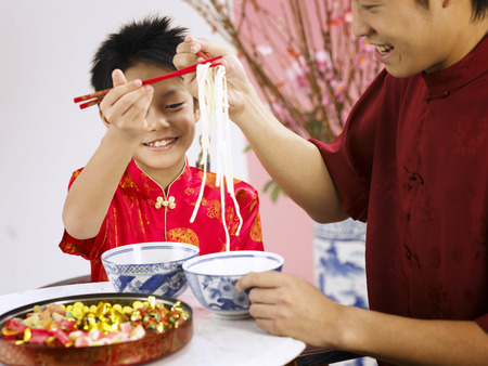 father and son eating longevity noodle during chinese new year
