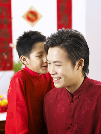 boy whispering to his father 写真素材