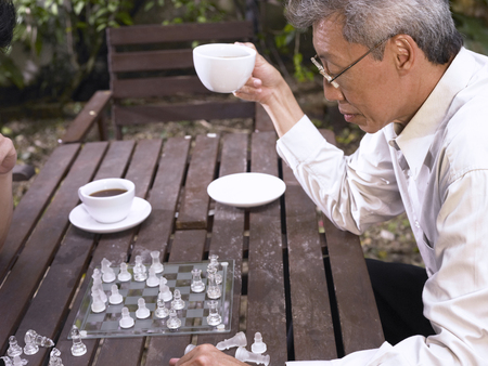 man hold a cup of coffee while playing chess with son