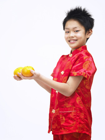 boy with mandarin oranges isolated on white Stock Photo