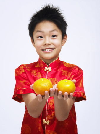 boy in traditional costume offering mandarin oranges