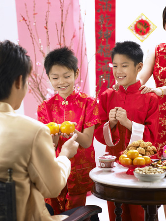 boys presenting mandarin oranges to their father with mother behind them Фото со стока