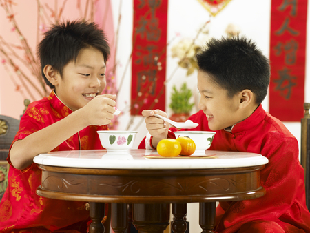boys having fun while eating rice balls Фото со стока