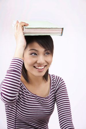 girl with book on the head on the plain background 版權商用圖片