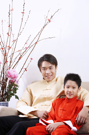 man and boy sitting in the living room with chinese new year decorations