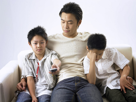 father and sons wathing avery boring tv programme Foto de archivo