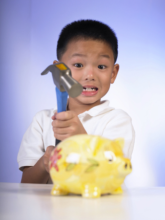 boy is breaking the the piggy bank 版權商用圖片