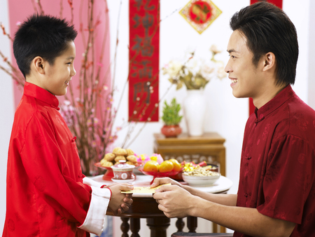 man giving red packet to boy