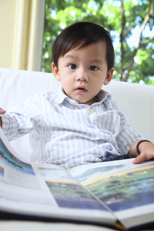 boy holding a book, looking at camera