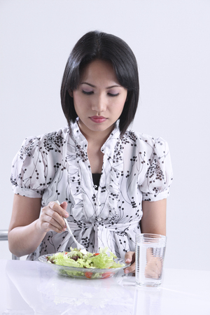 Young woman eating salad Stok Fotoğraf