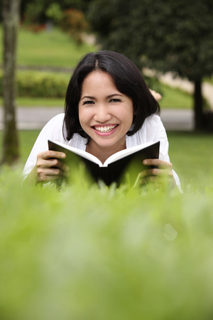 Young woman reading book outdoor, smiling 写真素材