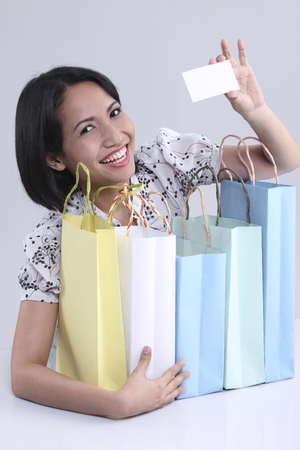 Woman holding business card and shopping bags