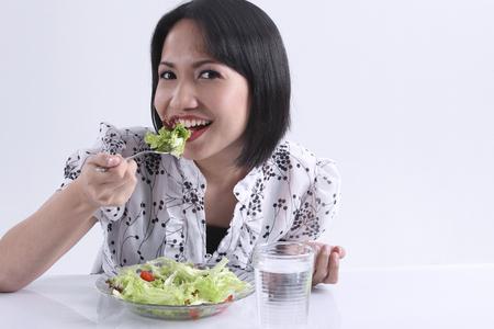 Young woman eating salad 写真素材