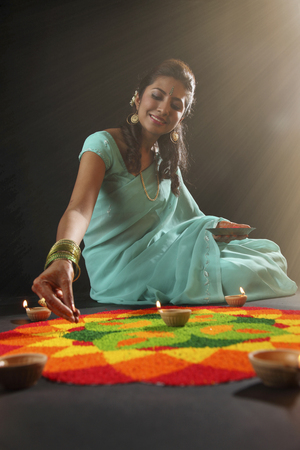young woman decorating rangoli with oil lamps Stock Photo