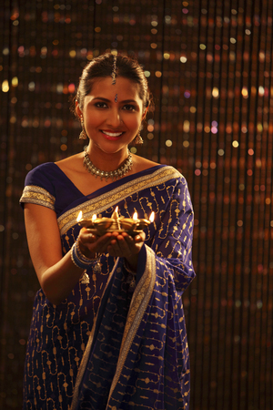 indian woman with blue sari holding oil lamp