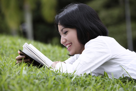 Woman reading at the park, smiling