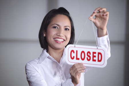 Young woman hanging Closed sign on door, smiling
