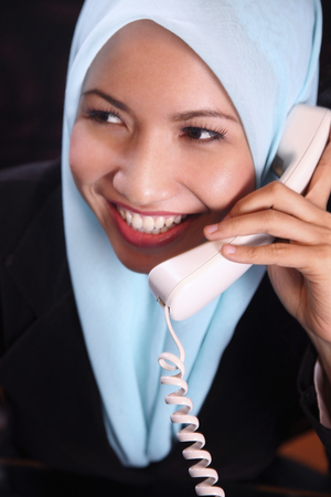 A smiling businesswoman answering phone call