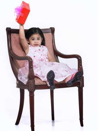 Little girl holding up a present sit in the chair isolated on white