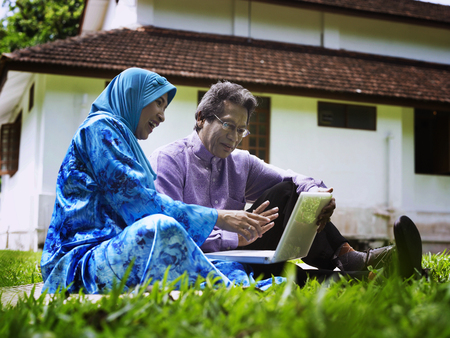 old couple using laptop in the garden
