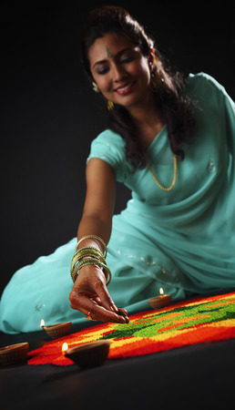 close up of  young woman decorating rangoli with oil lamps