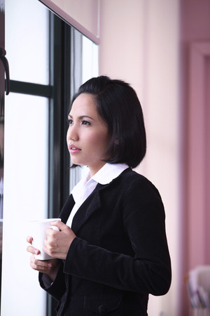 businesswoman with a mug, looking out of a window Фото со стока