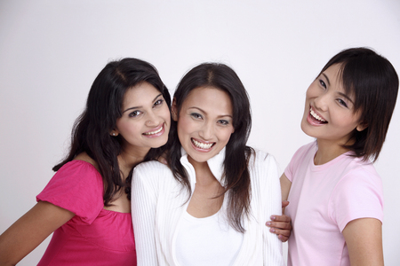 three friends happy and holding hands together Stock Photo