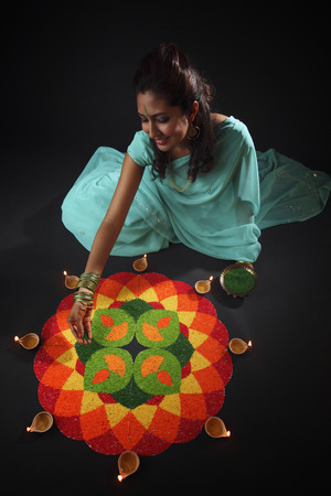High angle view of a young woman decorating rangoli with oil lamps Stock Photo