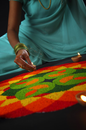 close up view of a young woman decorating rangoli with oil lamps