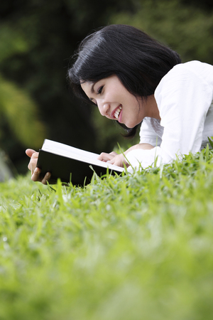 Young woman reading outdoor 写真素材