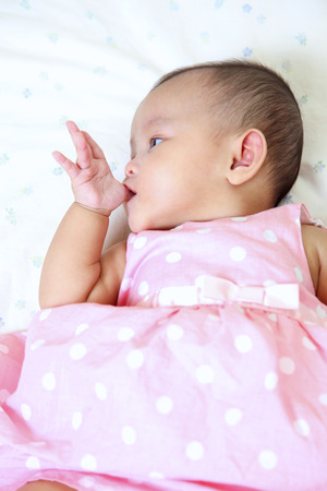 Side view of baby licking her thumb 免版税图像