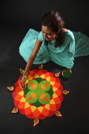 high angle view of a young woman decorating rangoli with oil lamps