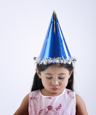 Liitle girl wearing birthday hat looking sad