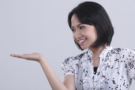 Side view of young woman with hand gesture