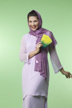 malay woman wearing baju kurung holding green packet