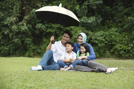 man holding umbrella for his family Standard-Bild